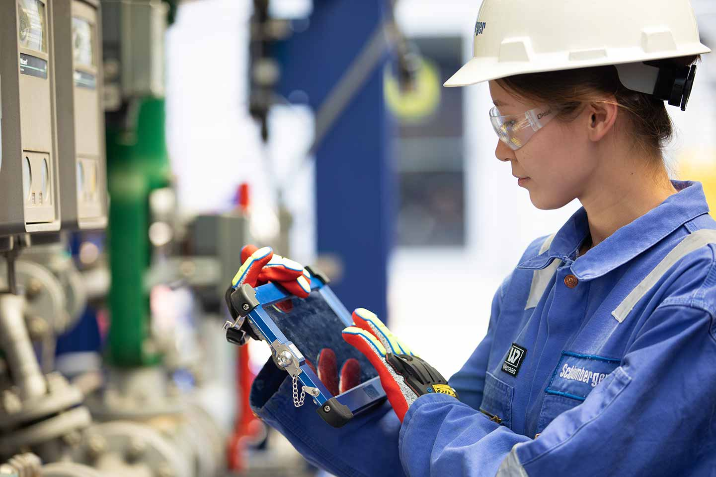 Schlumberger Worker Inspecting Equipment Wearing HSE Gear