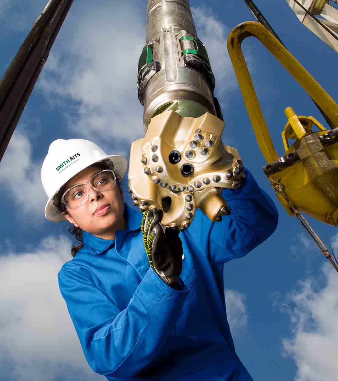 StingBlade - combo - female worker holding StingBlade drill bit on a rig.