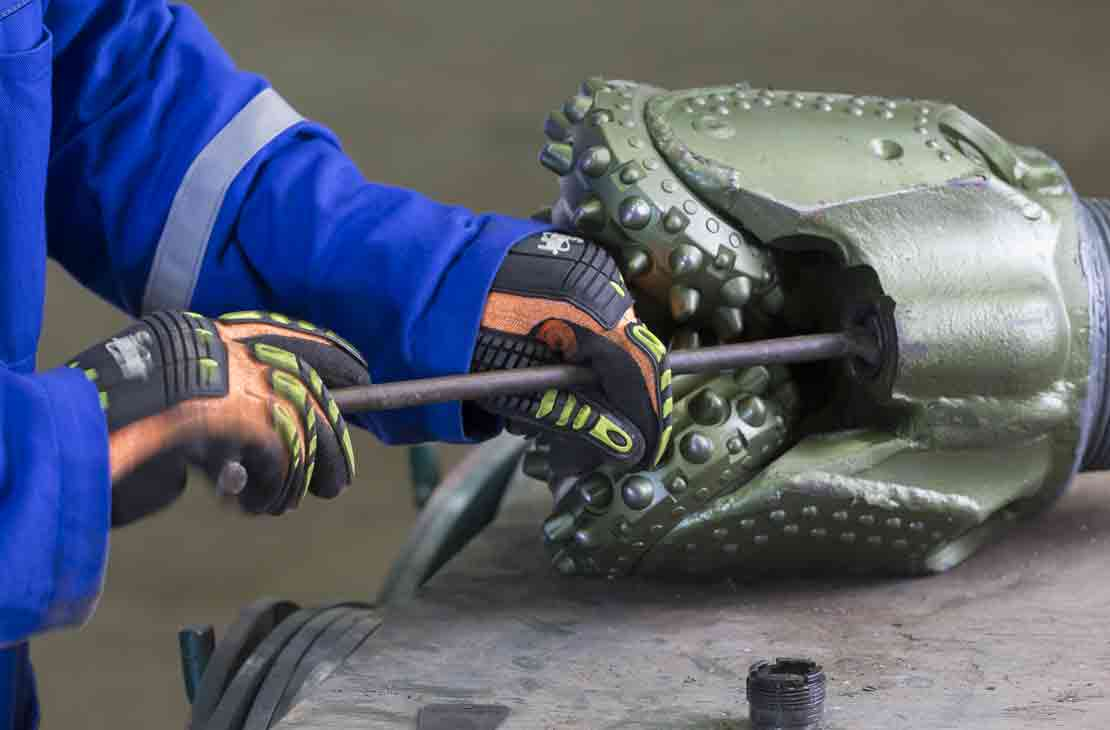 Technician installing nozzle on an Xtra roller cone bit