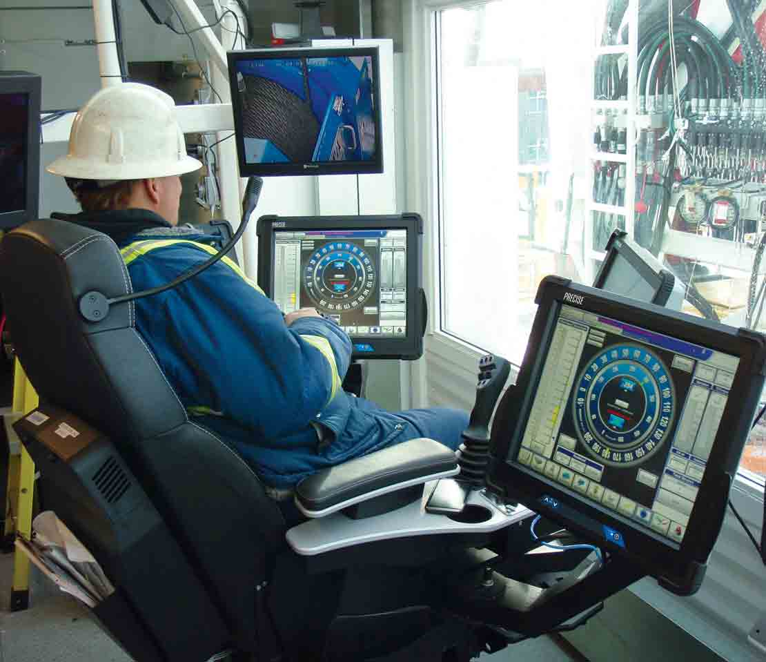 Operator sitting in a drillers chair with computer screens displaying PRECISE Automated Drilling System