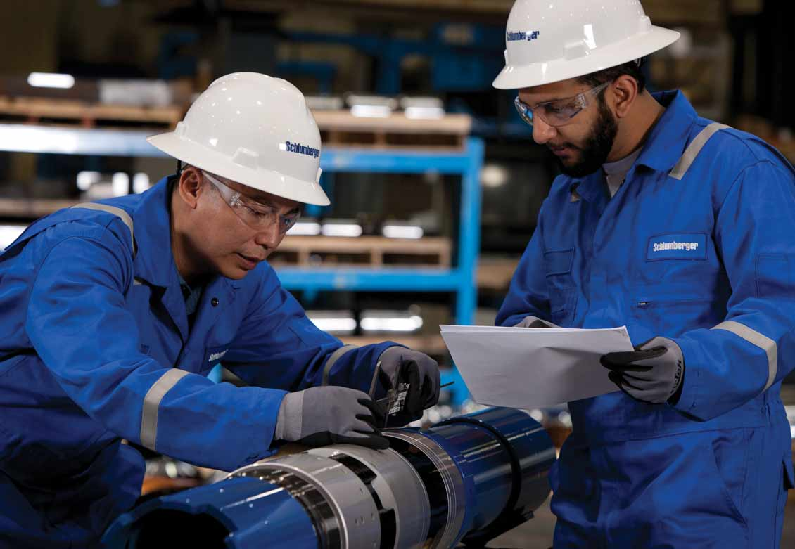 Two Schlumberger Worker Inspecting Liner Hanger