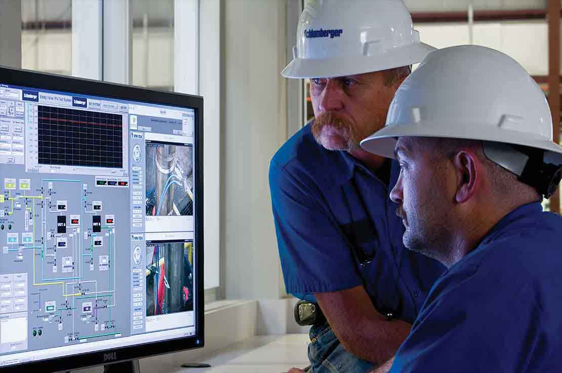 Two Schlumberger Workers Looking at a Monitor Displaying Data
