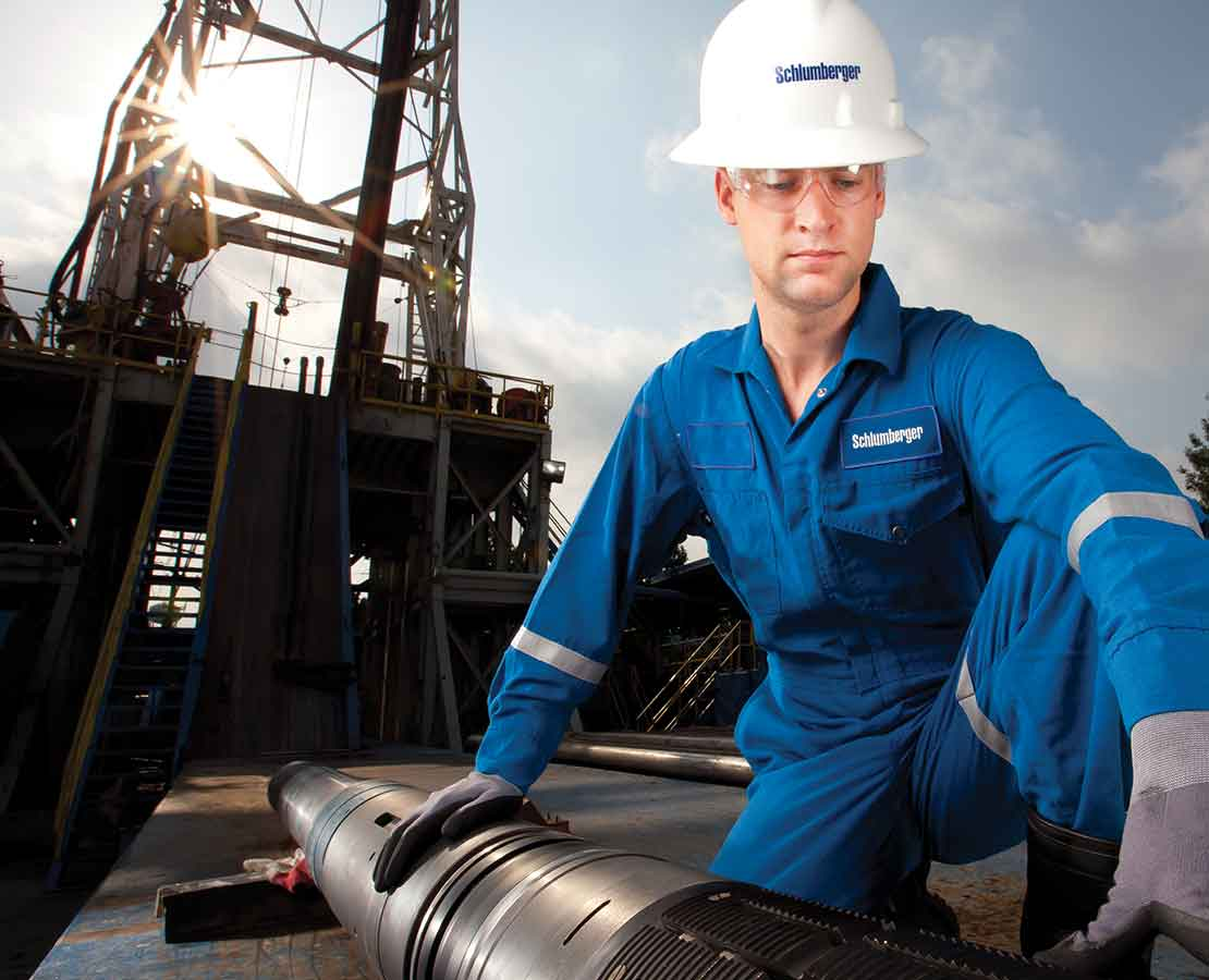 Schlumberger Worker On Rigsite Inspecting Tool