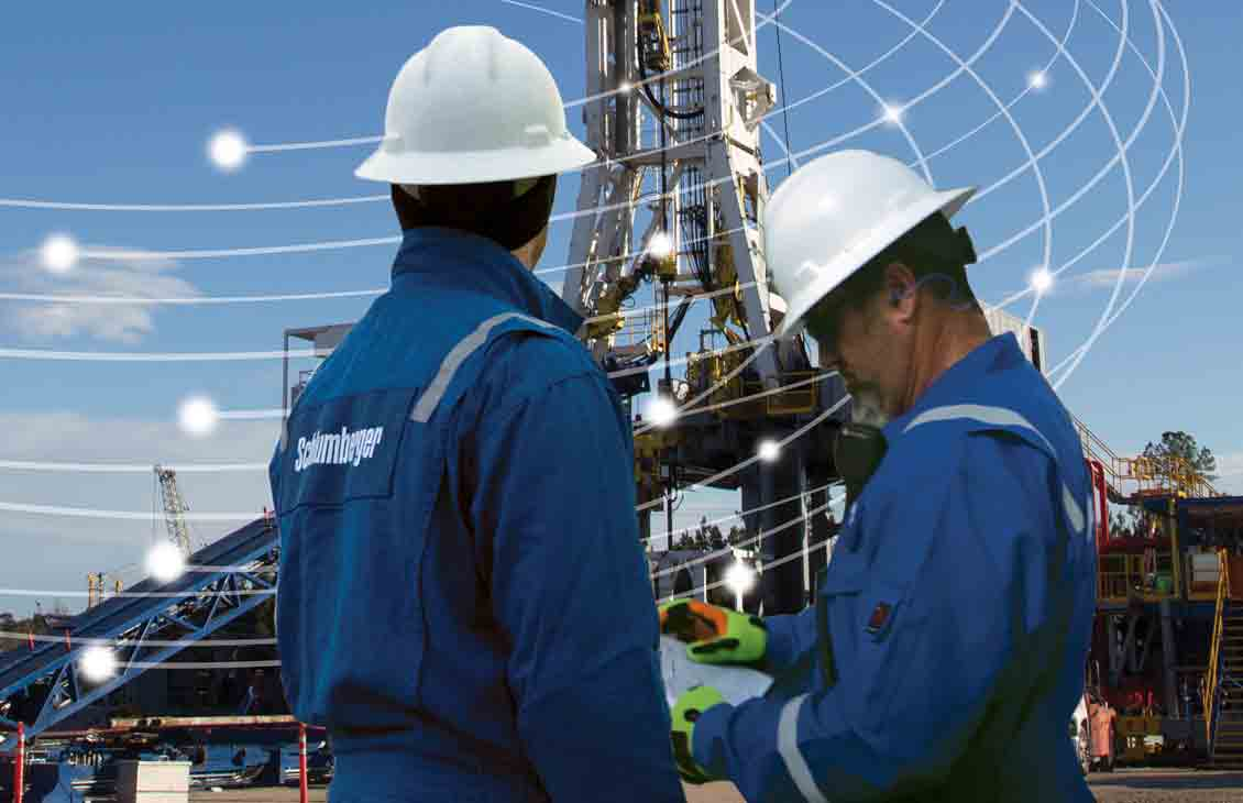Schlumberger field workers look up at a rig.