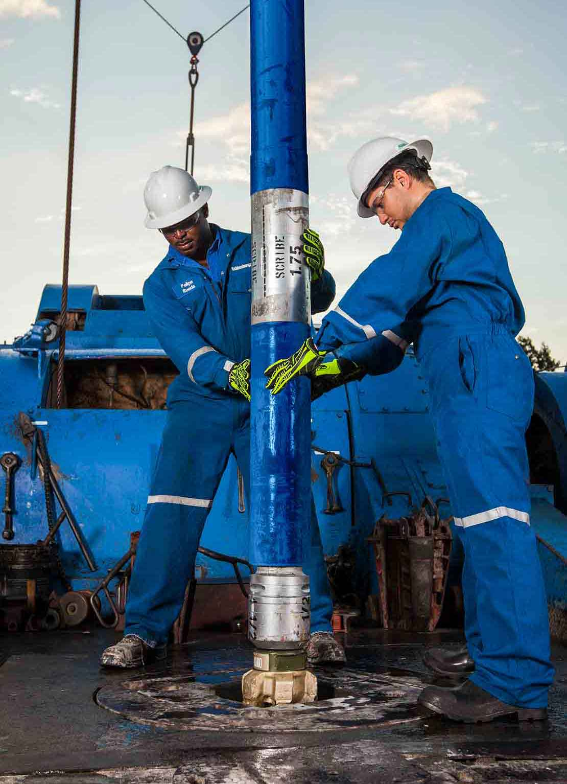 Two rig hands guide a clean BHA, including a PDC bit and drilling motor, down a well