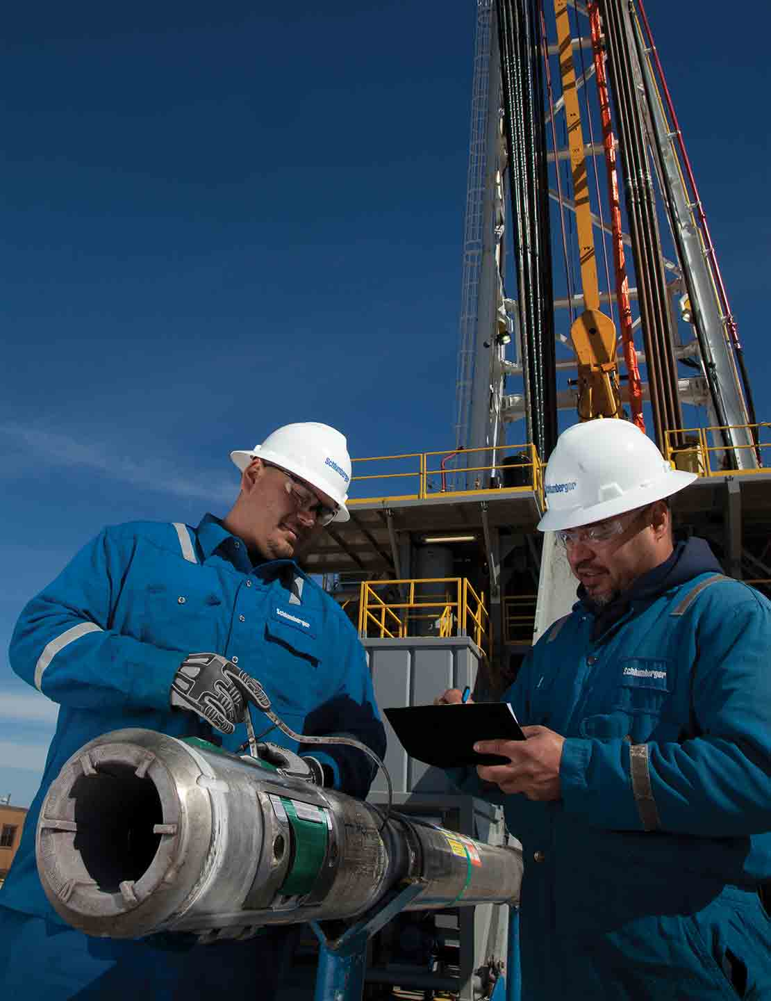 Two Schlumberger field technicians at a rigsite confirm specifications for a PowerDrive Orbit RSS prior to running downhole