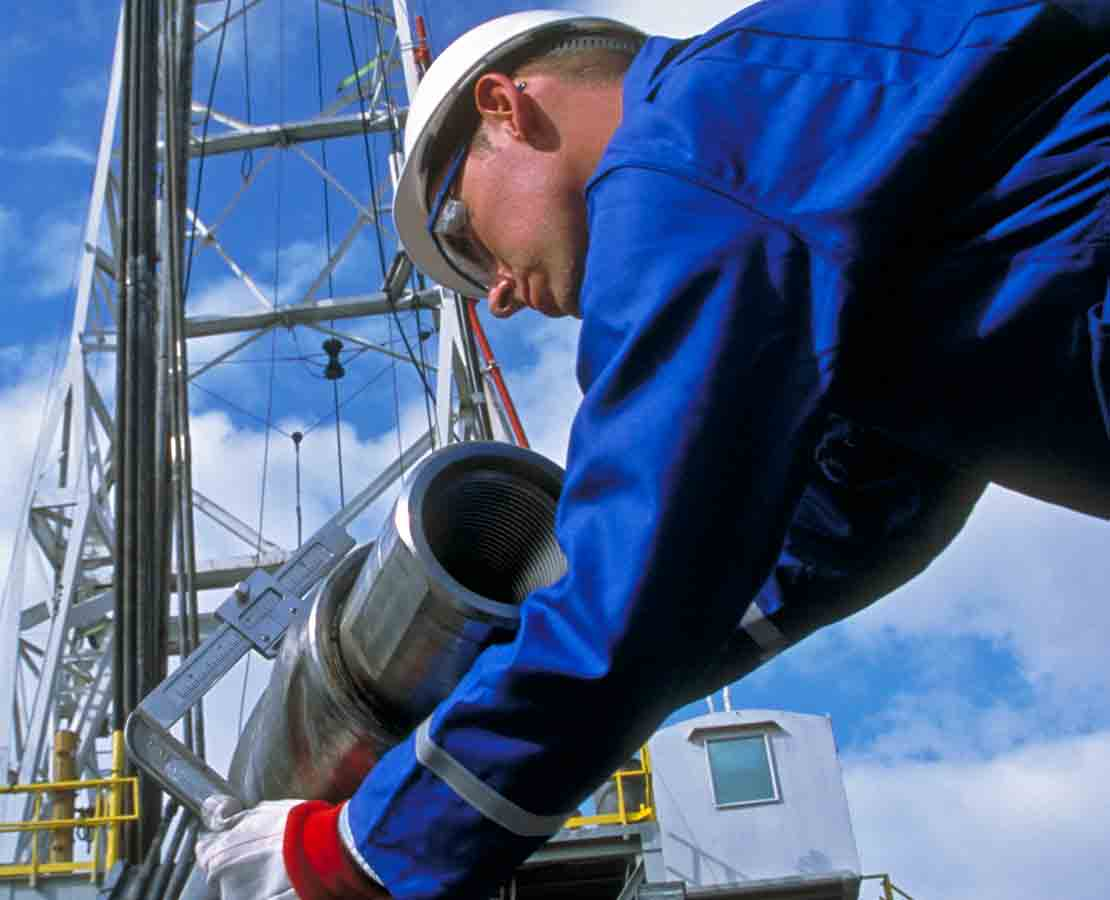A Schlumberger field technician at a rigsite verifies specifications on a PowerDrive vorteX RSS