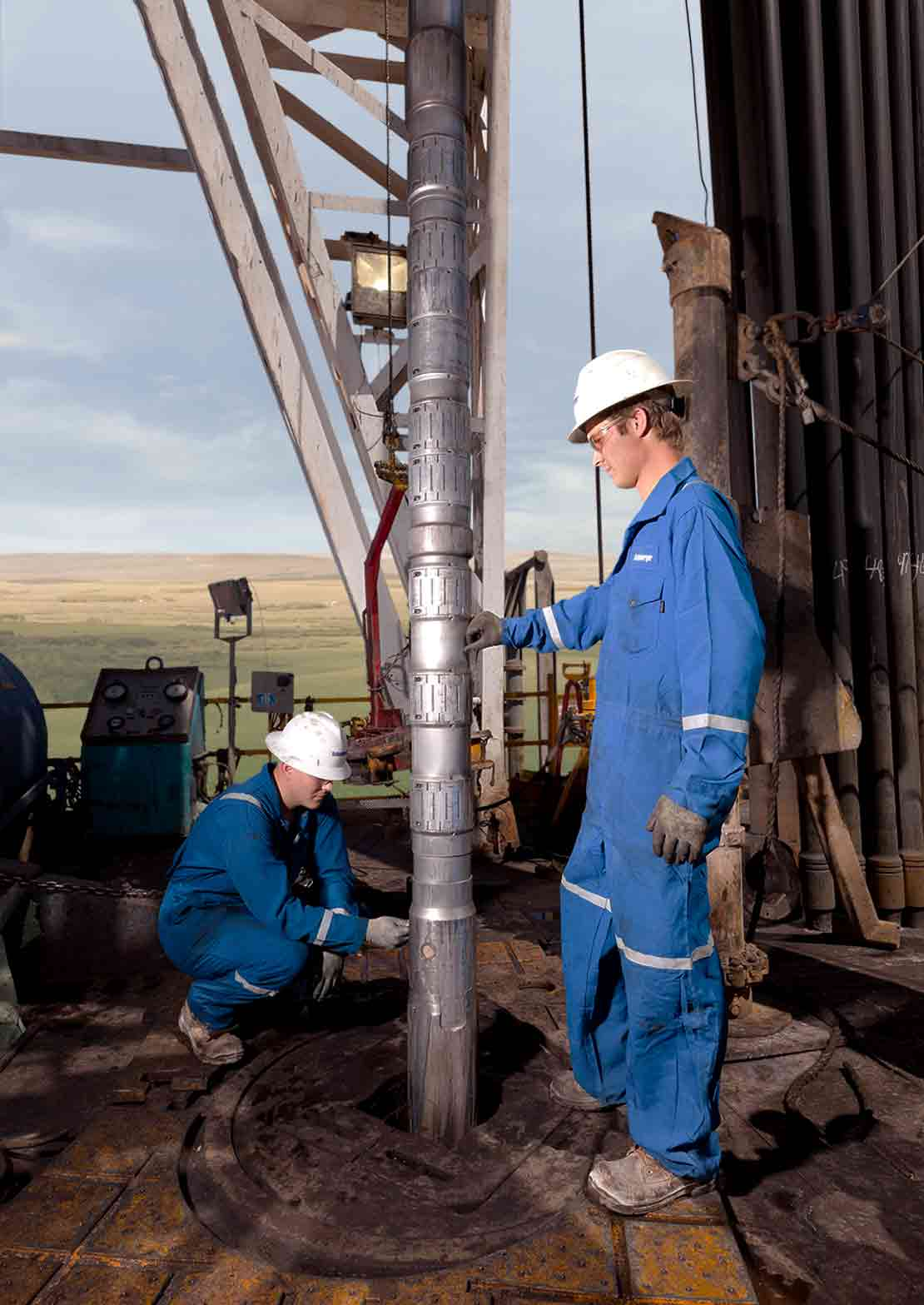 Two Schlumberger technicians adjust an LWD tool on a drilling rig floor