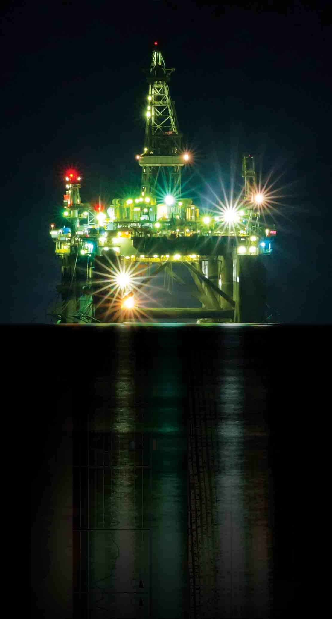 A deepwater rig at night whose reflection has been replaced with an LWD log from the SpectraSphere fluid mapping-while-drilling service
