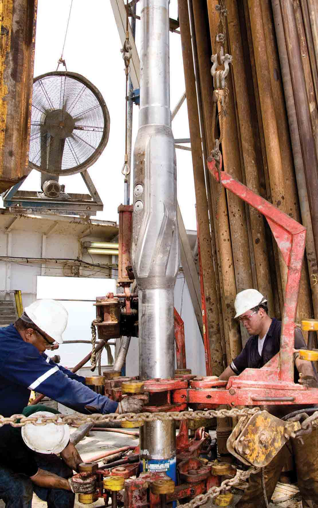 Three technicians preparing the StethoScope formation pressure-while-drilling service tool to go downhole with the aid of an iron roughneck