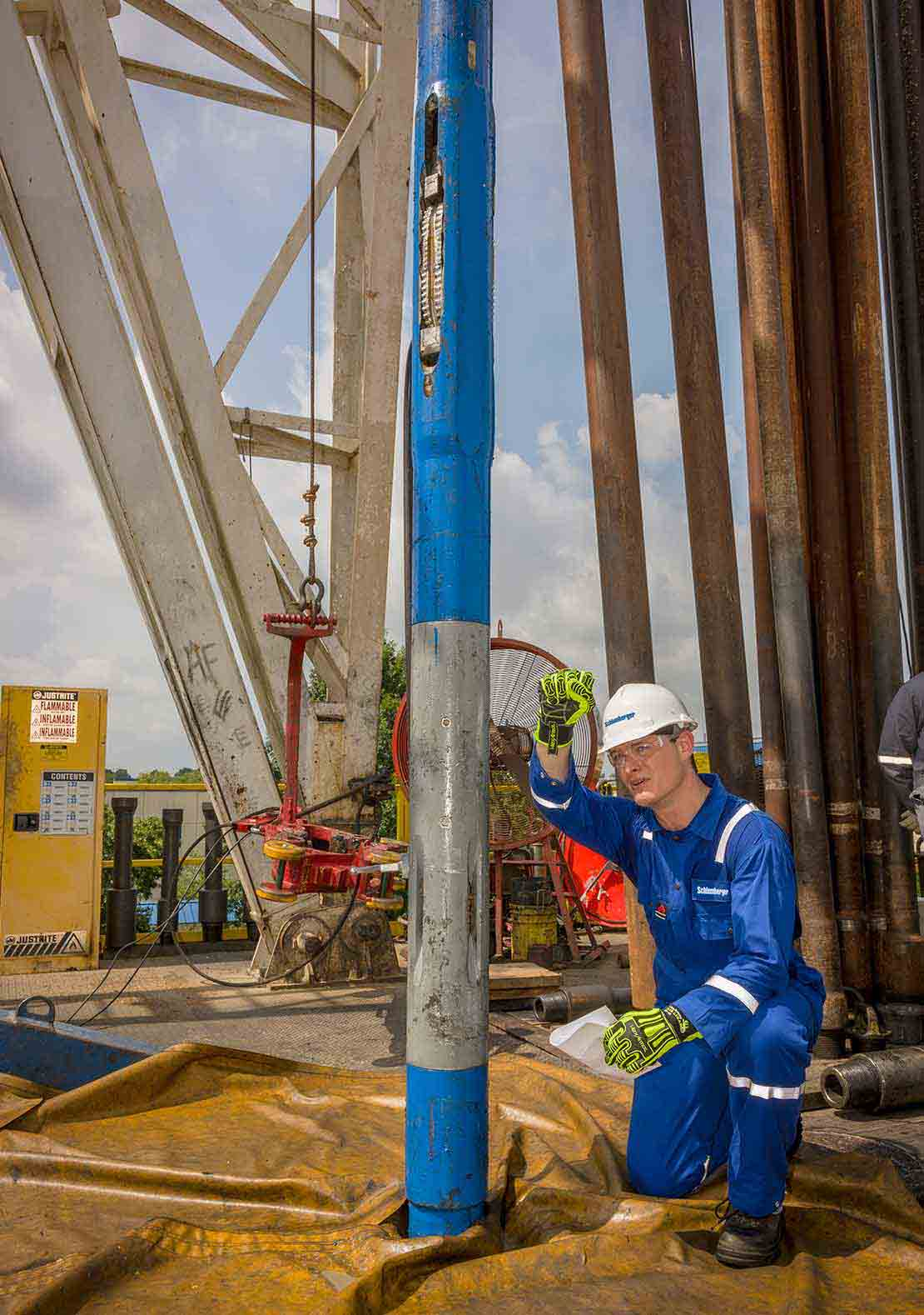 Schlumberger working kneeling down next to Rhino XC on-demand hydraulically actuated reamer on rigsite.