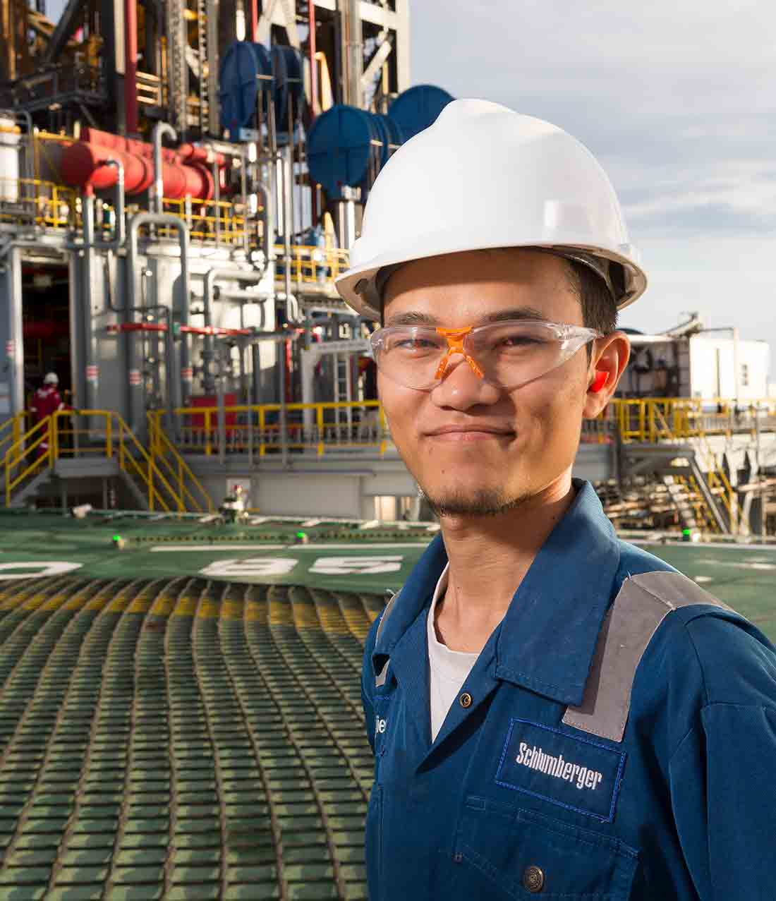 Man standing on deck of an offshore oil rig.