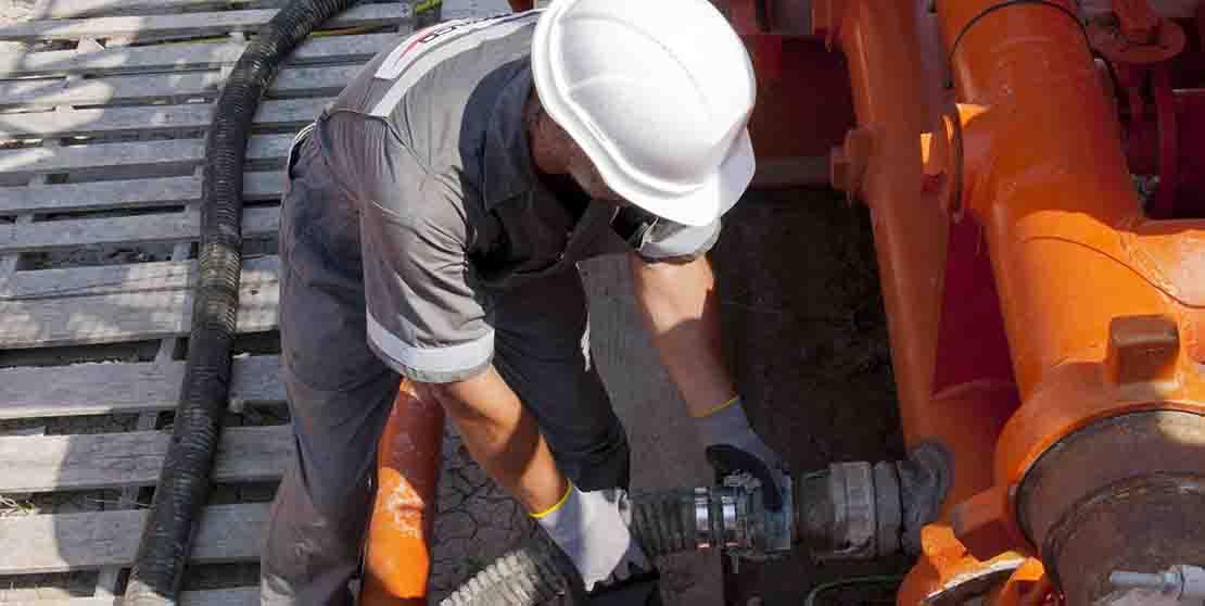 M-I SWACO employee fitting hose into orange tank.