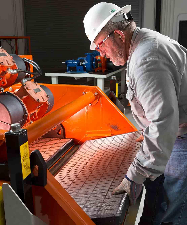 A technician inserts a new DURAFLO screen into a shaker