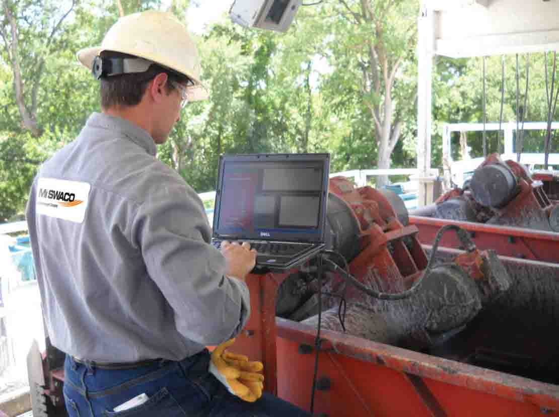 Man at computer in front of shale shaker in use.
