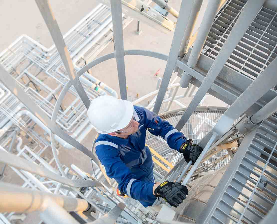 Schlumberger worker performing maintenance at a processing facility.