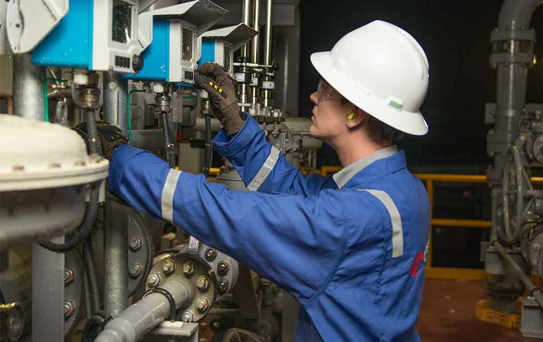 Man testing valve at oil treatment facility