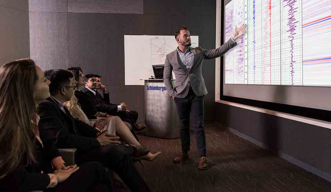 Presenter giving a speech to a crowd with seismic data in the background