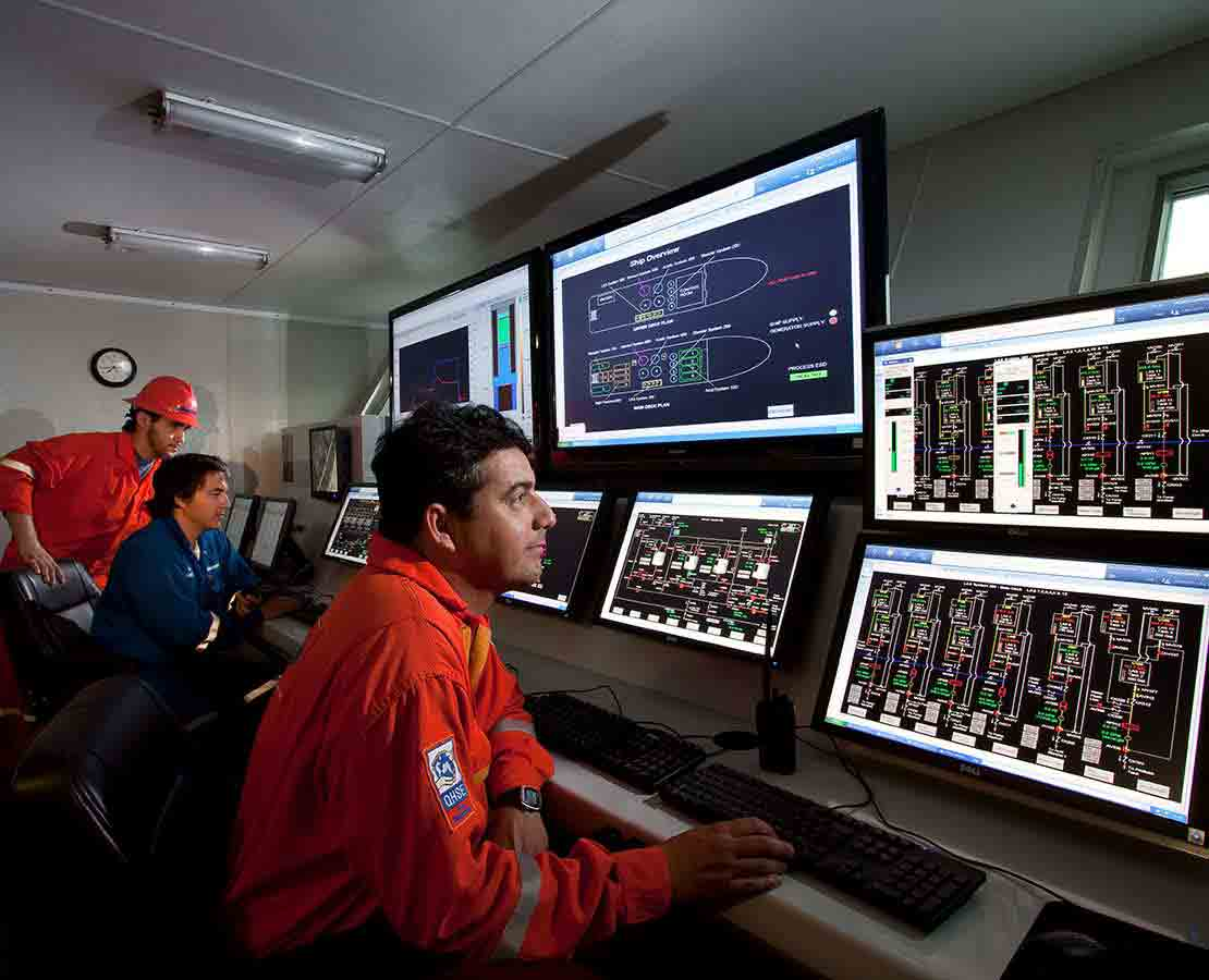 Schlumberger Workers in a DeepSTIM stimulation vessel Viewing Data on Monitors