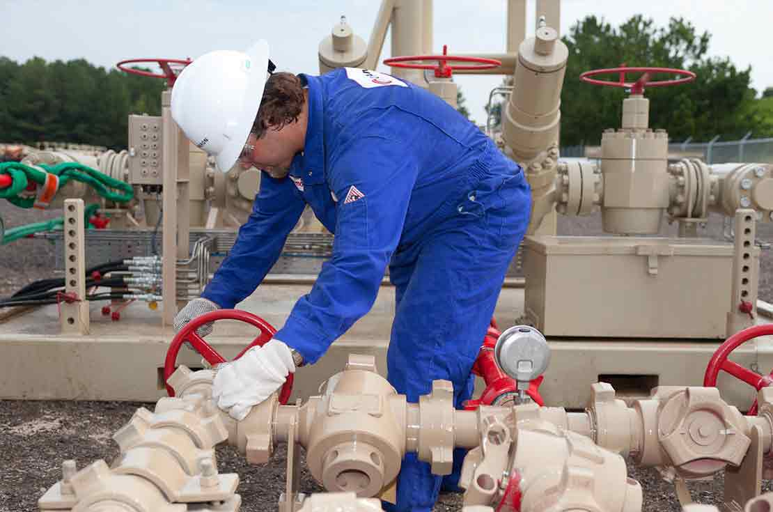 Cameron Worker Performing Maintenance Check on Plug Valve Choke Manifold in the Field