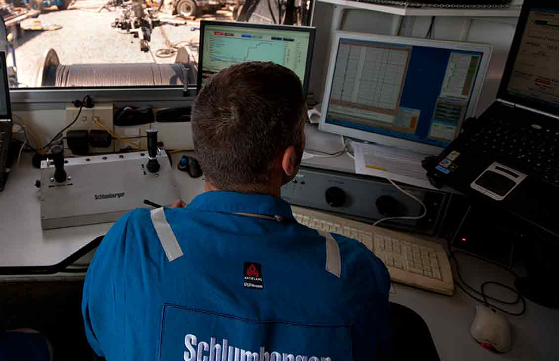 Schlumberger worker using FracCAT fracturing computer-aided treatment system while looking at monitors on rigsite.