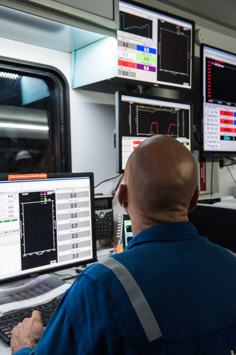 Schlumberger worker looking at monitors displaying data.