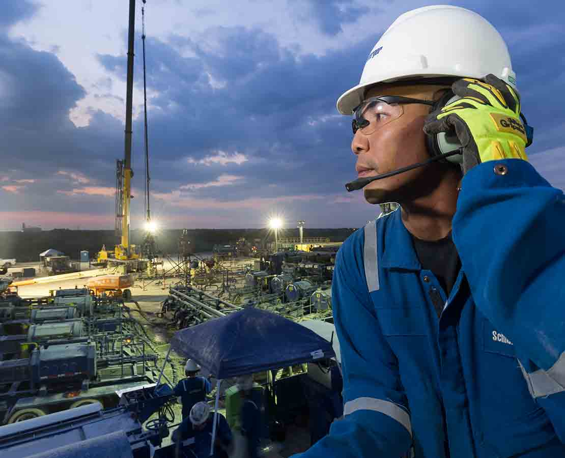 Schlumberger worker looking at the rigsite during night operations.