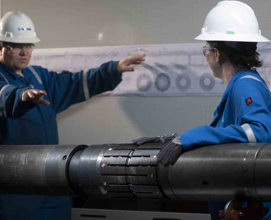 Two Schlumberger workers discussing the tool as part of the CERTIS high-integrity reservoir test isolation system.