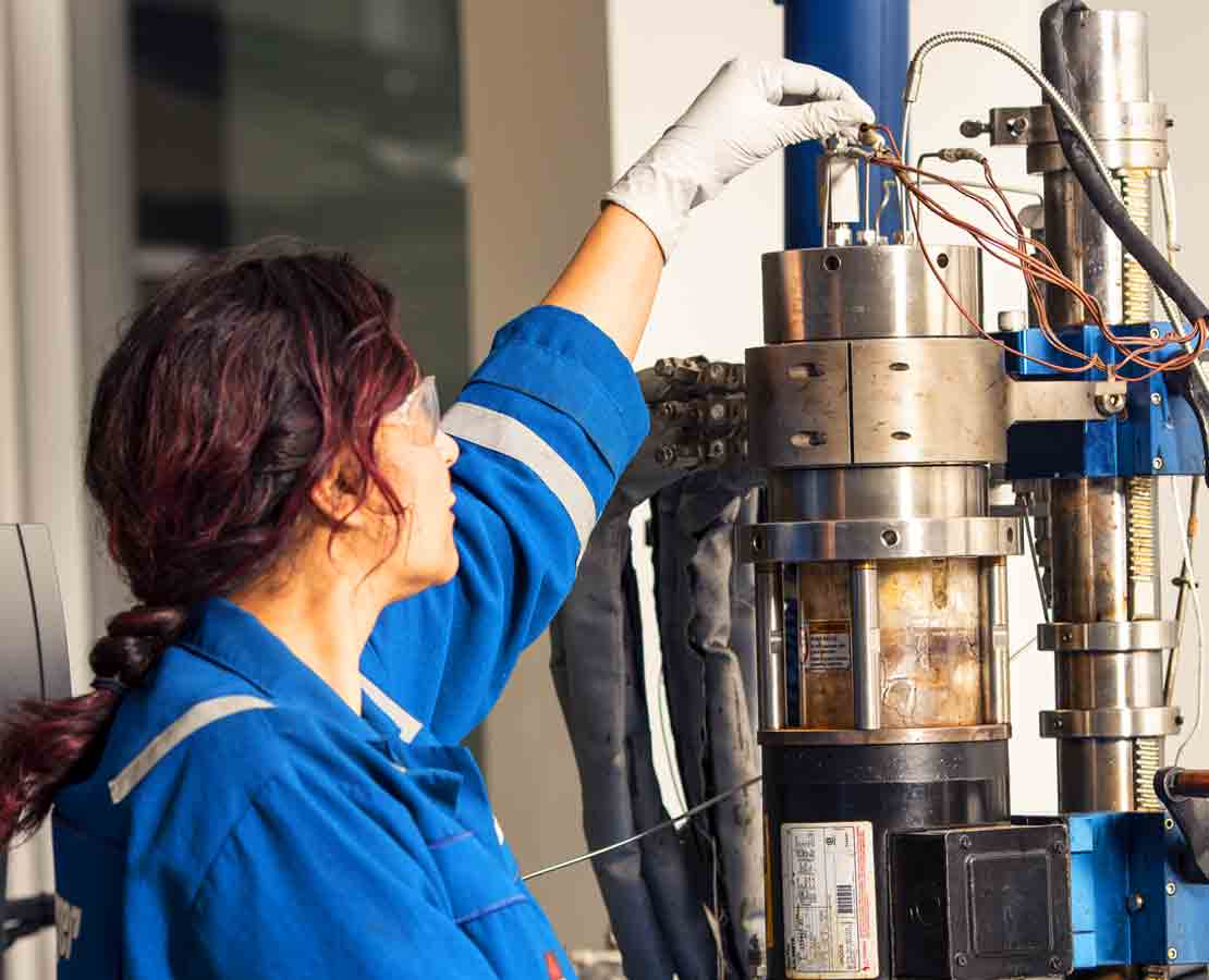 Schlumberger worker looking into microscope while performing analysis related to flow assurance rheology.