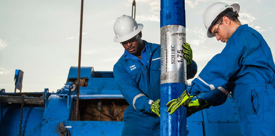 Two men holding tool on the rig with blue abstract background.