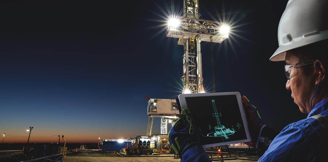 Man looking at a tablet with digital rendering of the rig in front of the land rig at night.