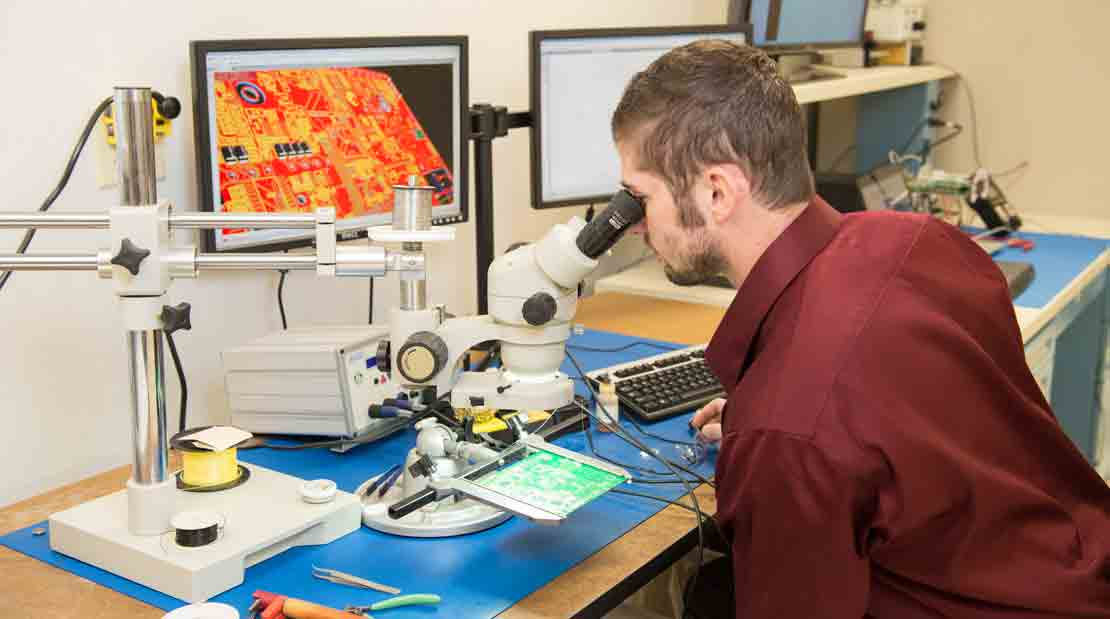Technician looking at a circuit board through a microscope