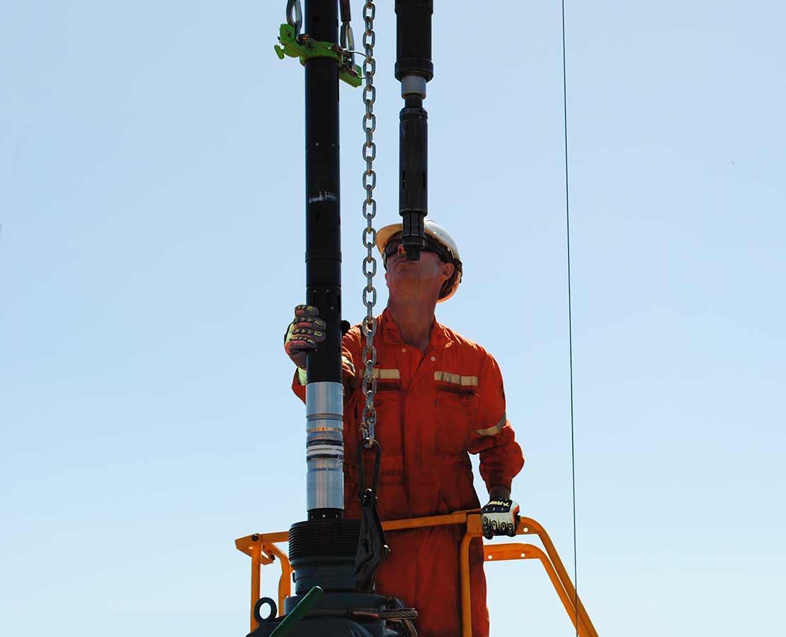 Schlumberger worker holding a SIMultra retrievable bridge plug.