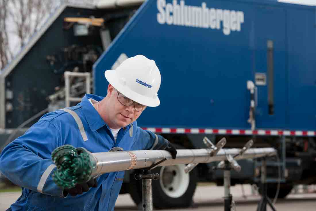A Schlumberger employee at the back of a Wireline truck inspecting the RESOLVE milling tool.